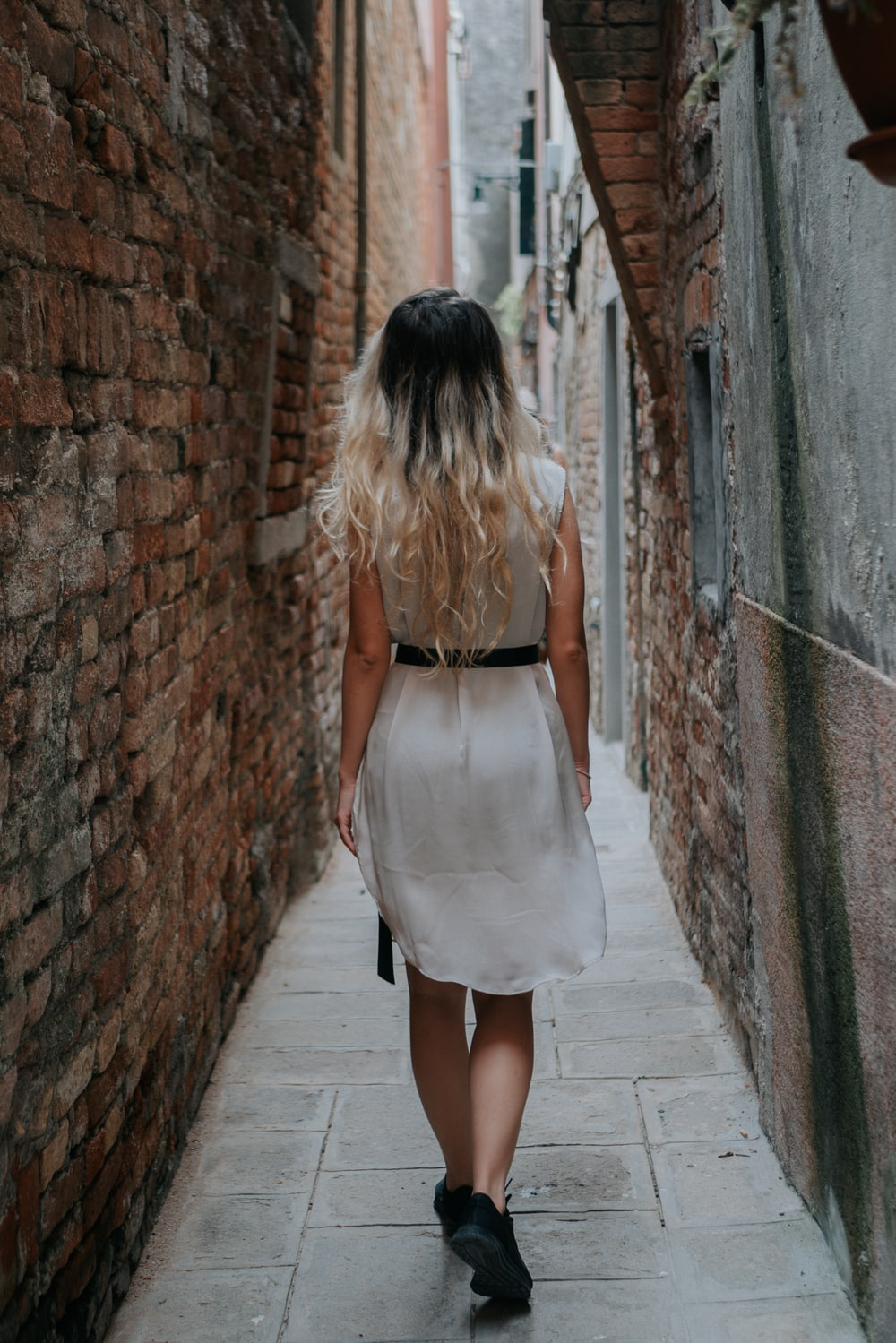 woman in white dress standing on gray concrete brick wall during daytime