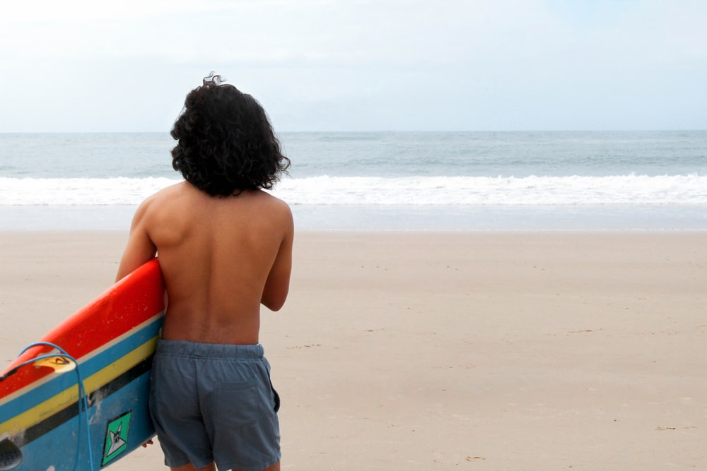topless boy in black shorts standing on beach during daytime