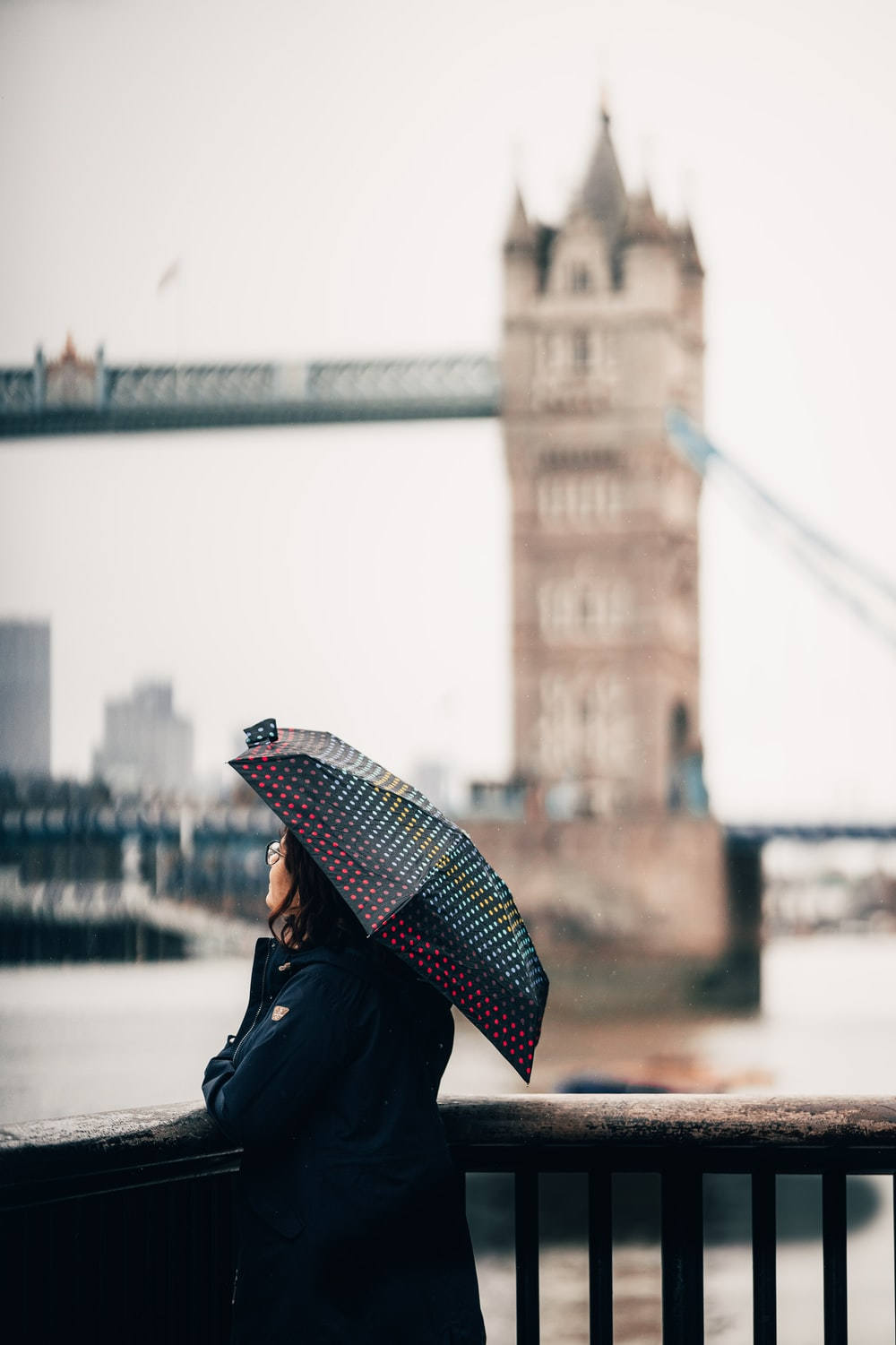 woman in black jacket holding red and white umbrella