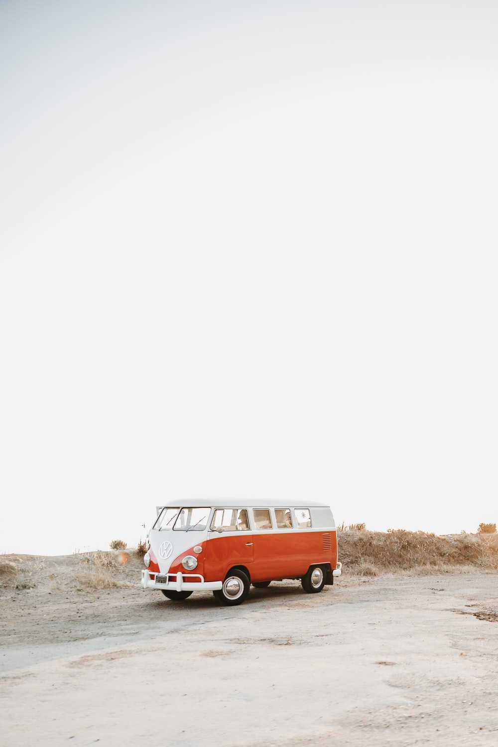 red and white volkswagen t-1 on brown sand during daytime