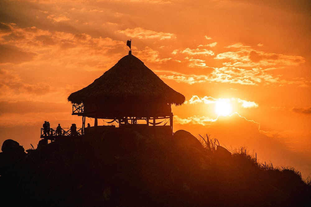 silhouette of people standing near brown wooden gazebo during sunset