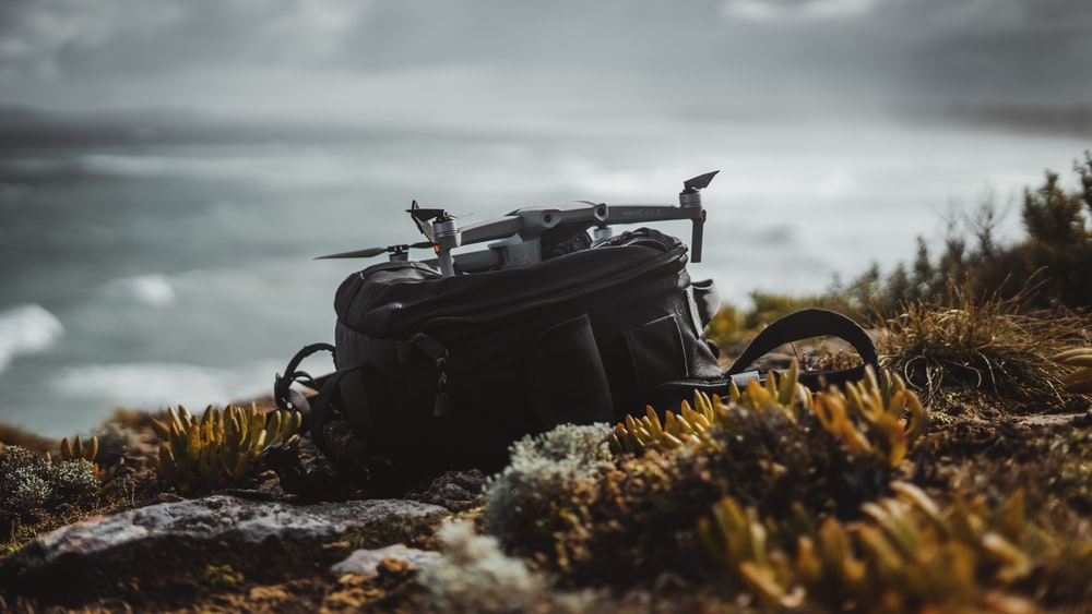 black leather backpack on rocky shore during daytime