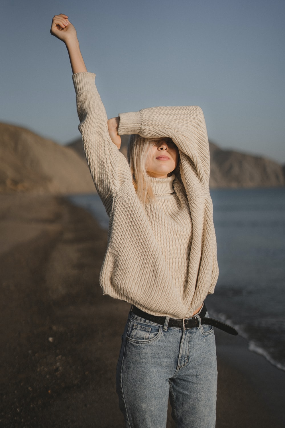 woman in beige knit sweater and blue denim jeans standing on beach shore during daytime