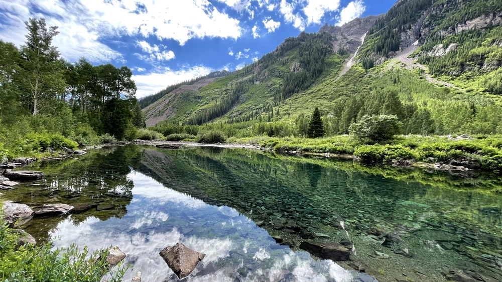 green trees and mountain beside river under blue sky during daytime