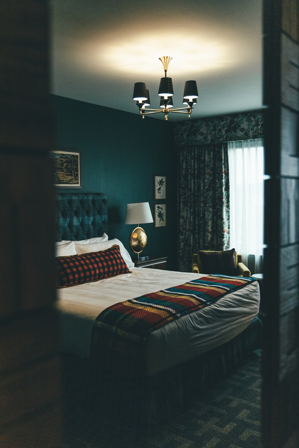 black and white floor lamp near bed