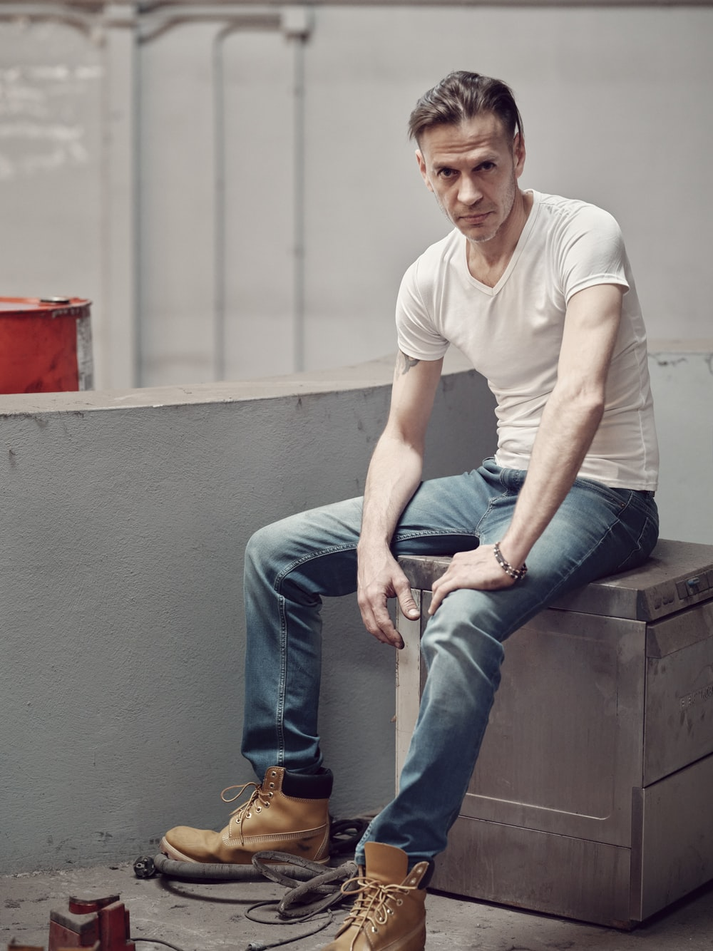 man in white crew neck t-shirt and blue denim jeans sitting on gray concrete bench