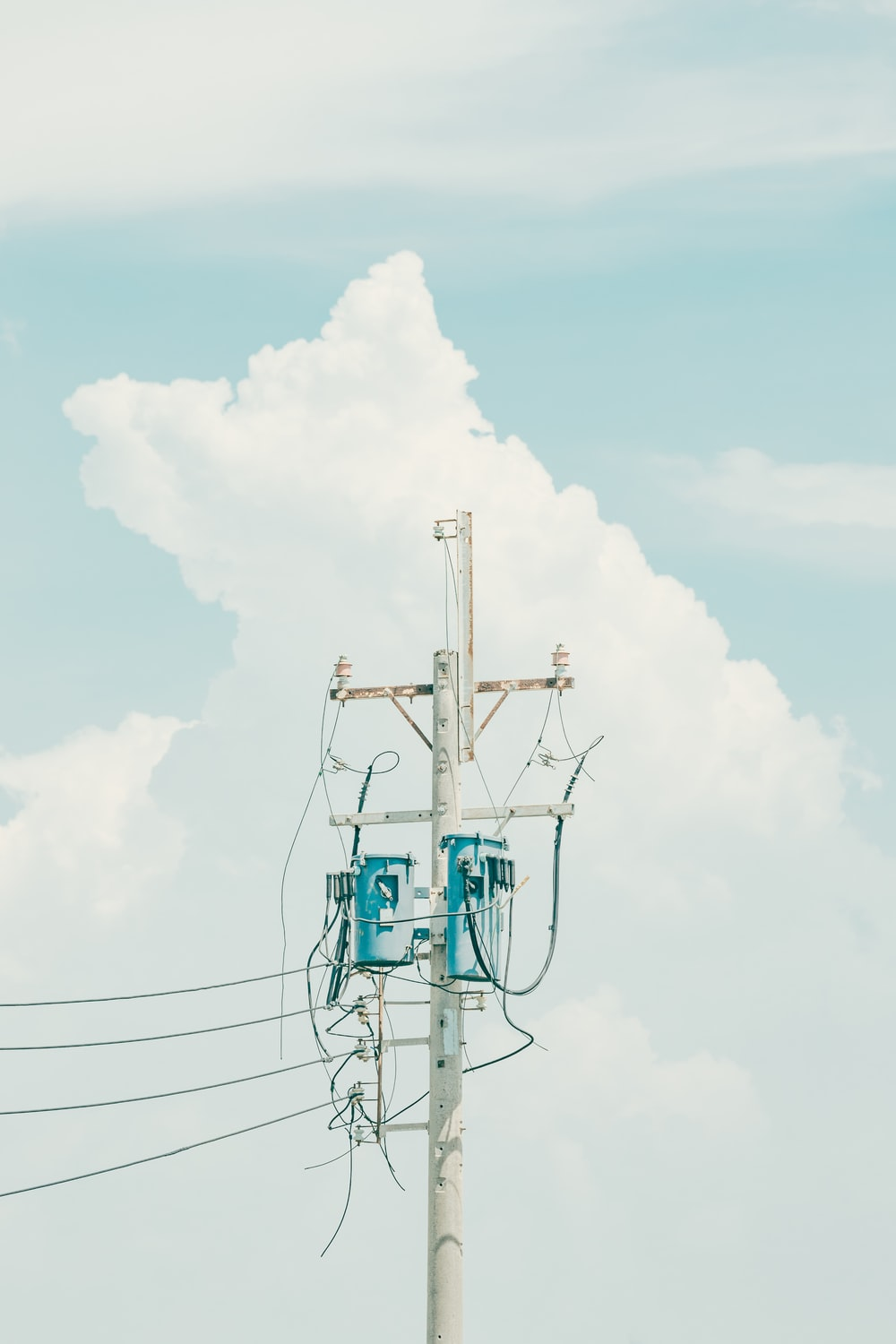 white and blue electric tower under white clouds