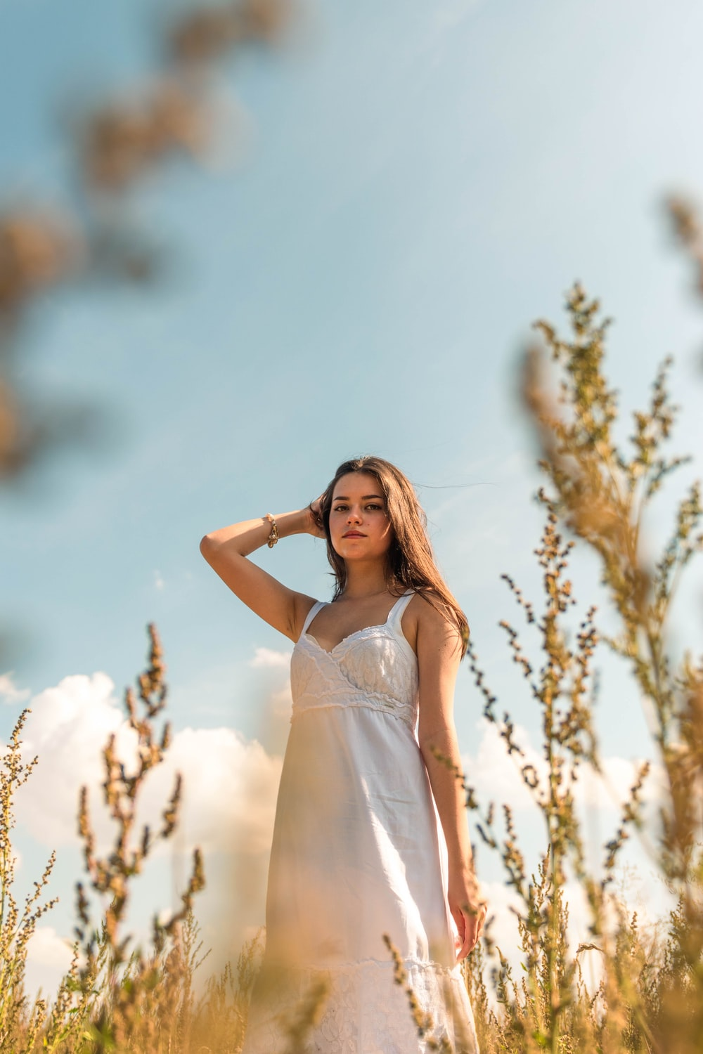 woman in white spaghetti strap dress standing near brown tree during daytime