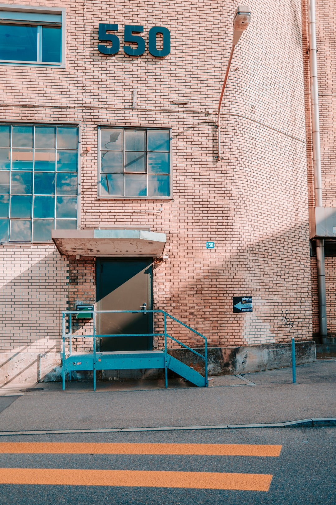 blue metal ladder beside brown brick building