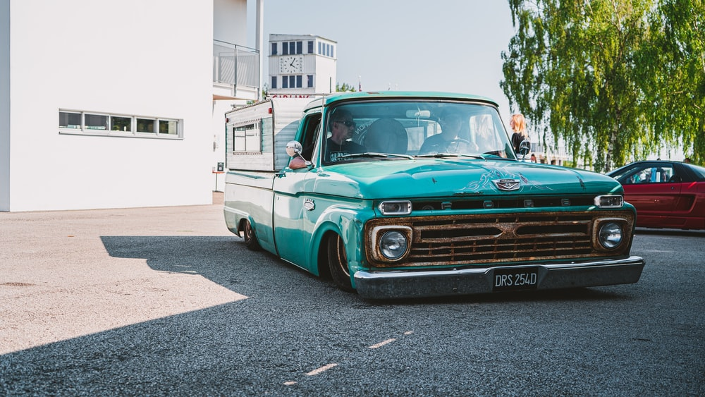 teal and white chevrolet single cab pickup truck parked on gray concrete road during daytime
