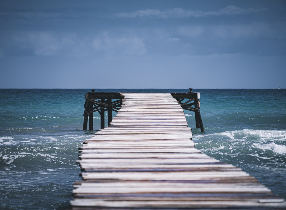 brown wooden dock on sea during daytime