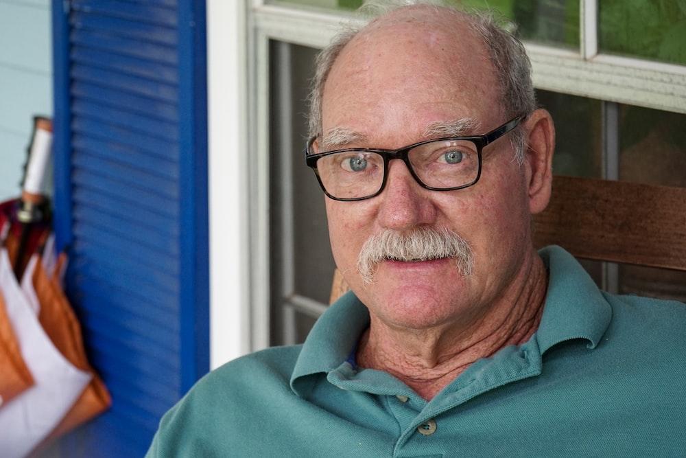 man in green polo shirt wearing black framed eyeglasses