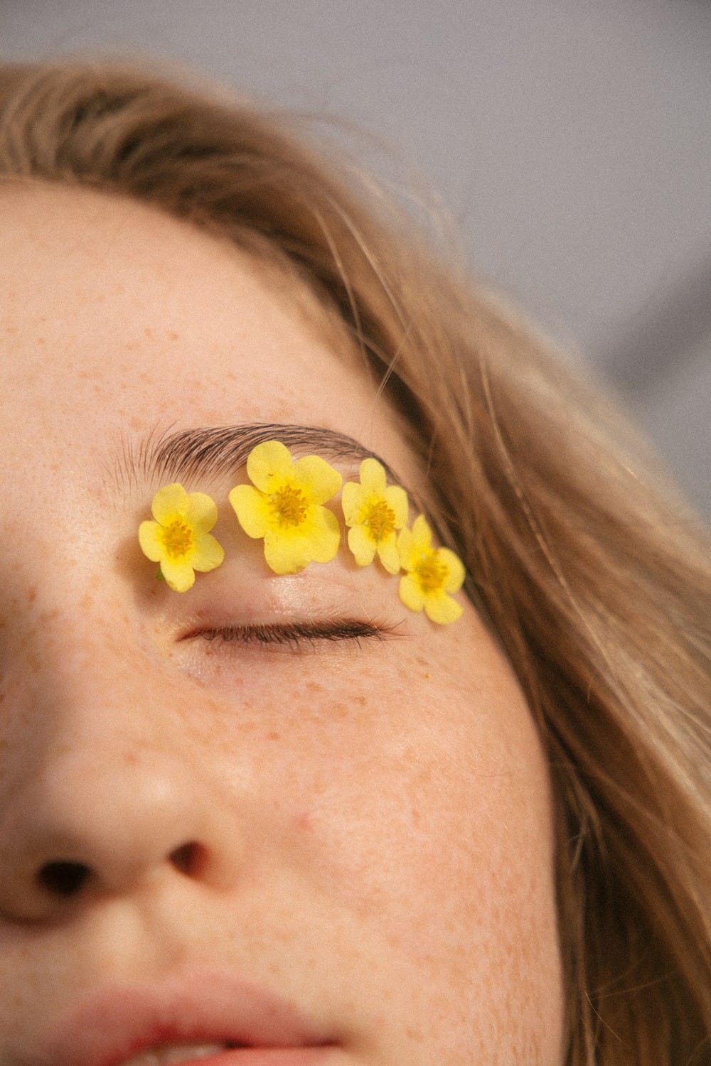 woman with yellow flower on her ear