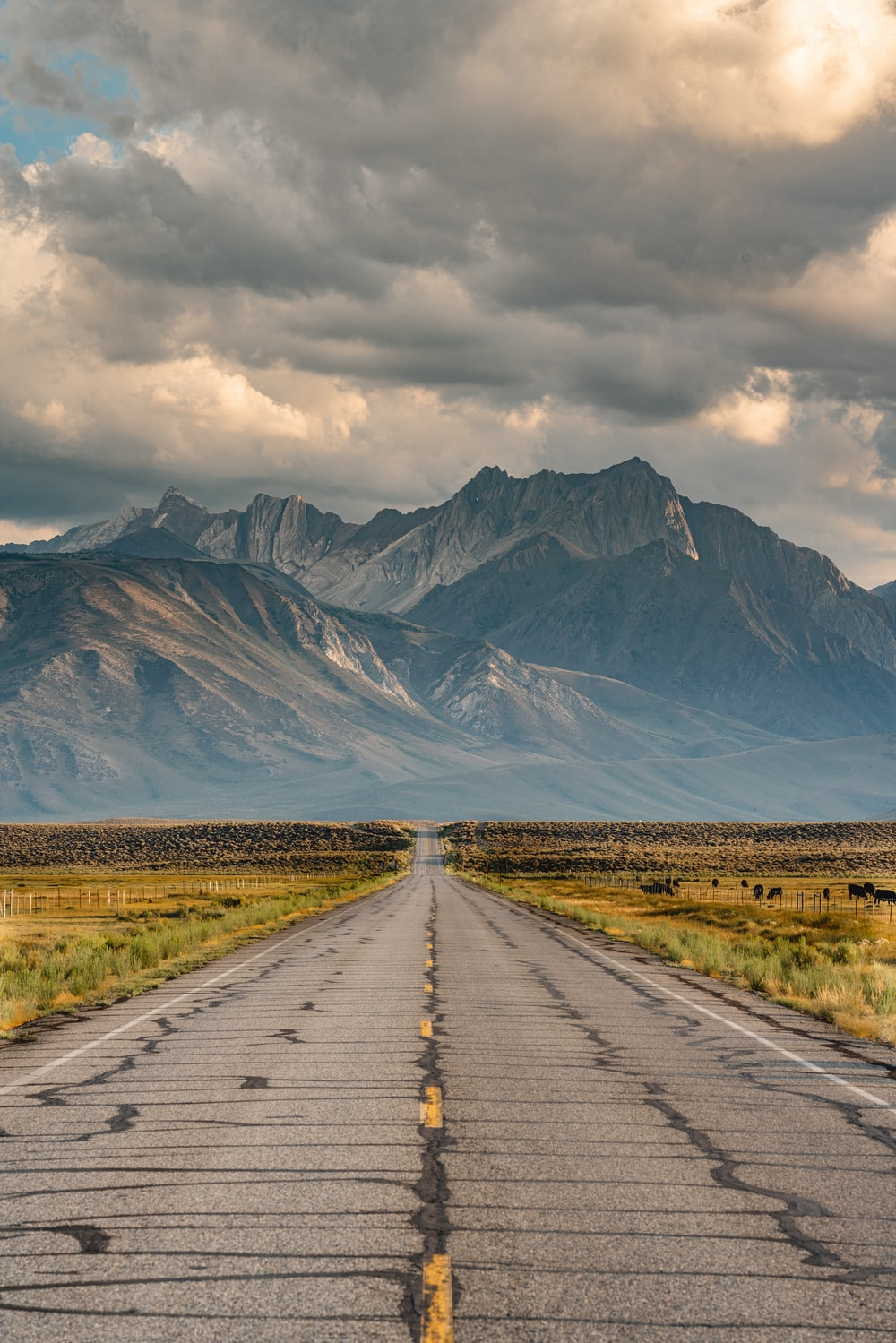gray concrete road between green grass field near mountain under white clouds during daytime