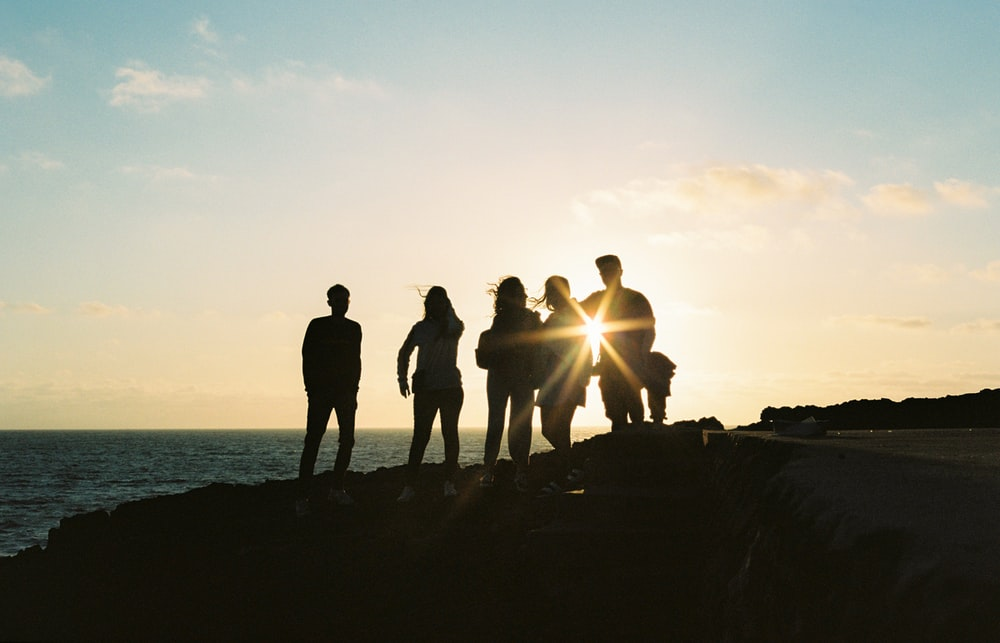 silhouette of people standing on rock formation near body of water during sunset