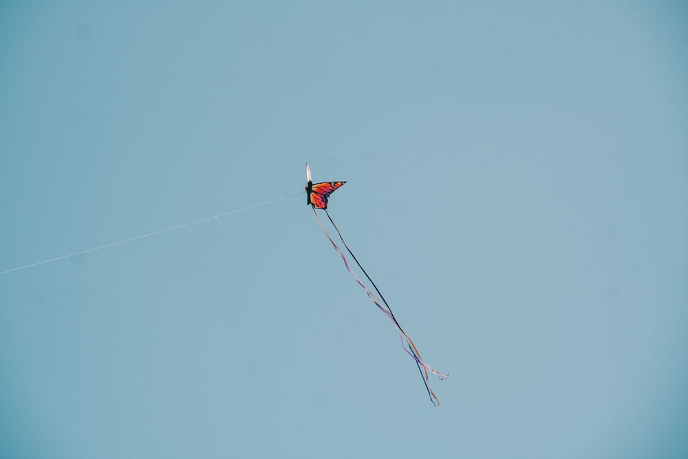 red and white kite flying in the sky
