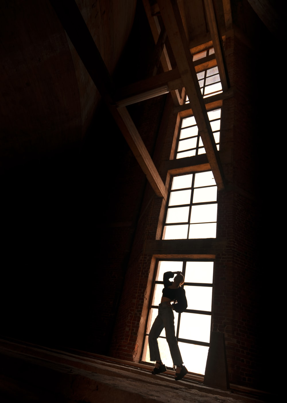 silhouette of person standing on window