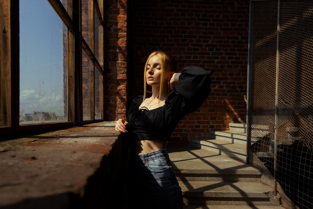 woman in black long sleeve shirt and black skirt standing near brown brick wall during daytime