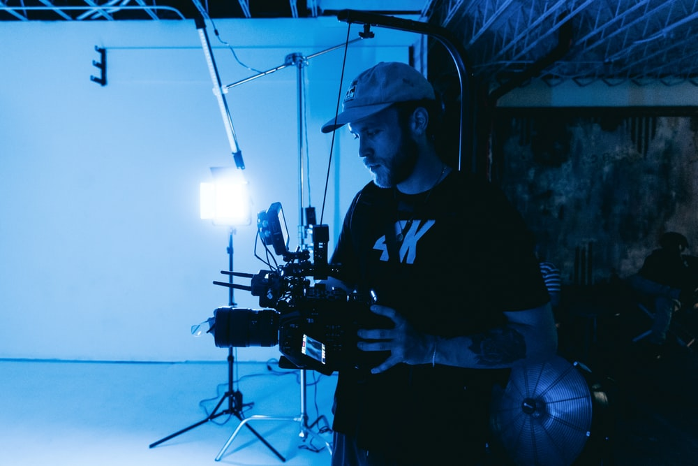 man in black crew neck t-shirt standing near black camera