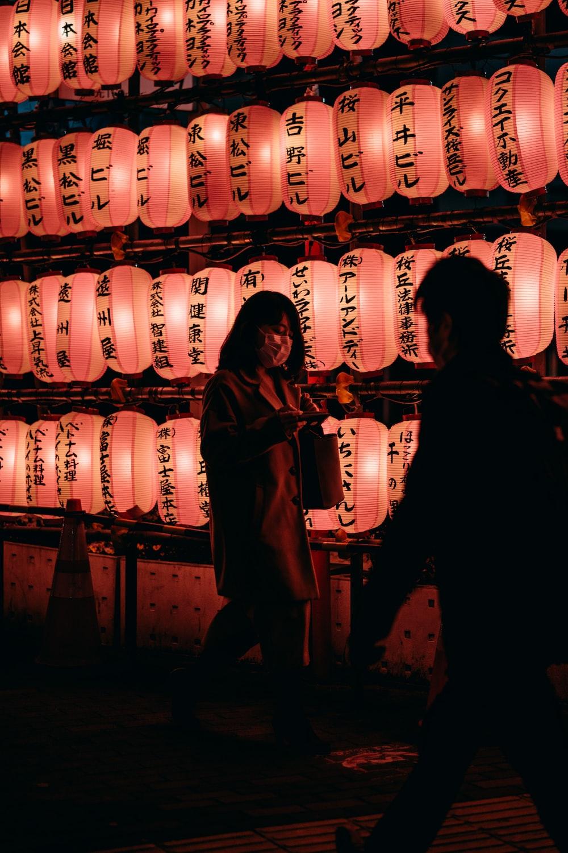man in black jacket standing beside brown wooden barrels
