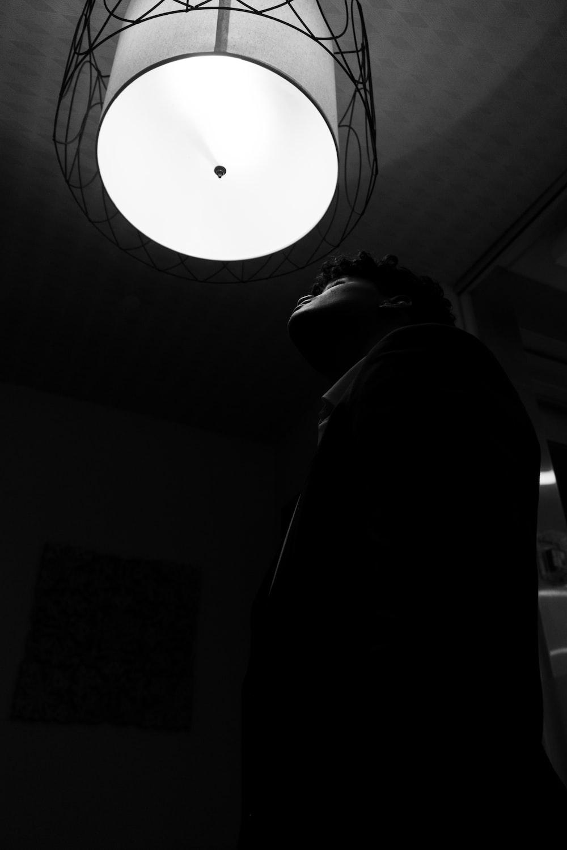 man in black hoodie under white ceiling lamp