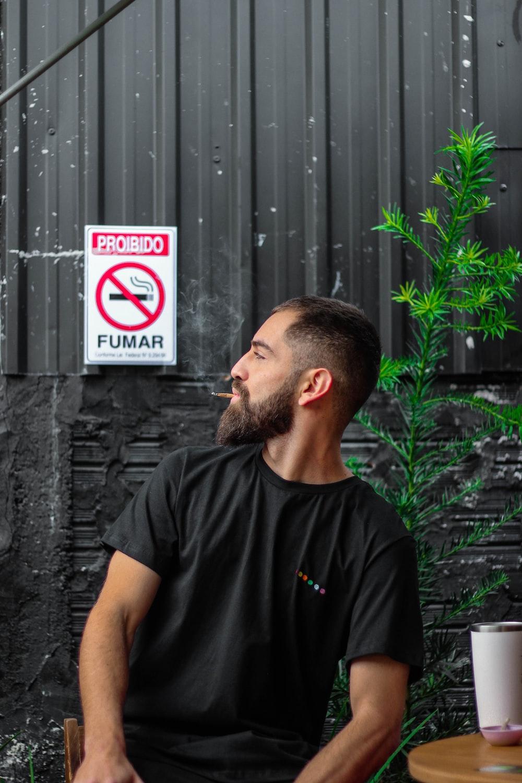 man in black crew neck t-shirt standing beside gray wall