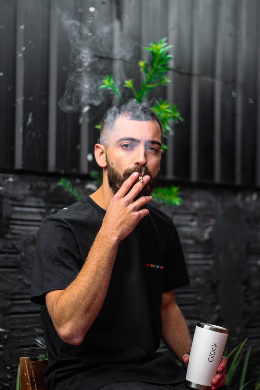 man in black polo shirt smoking cigarette