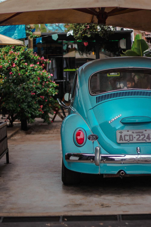 blue volkswagen beetle parked on sidewalk during daytime