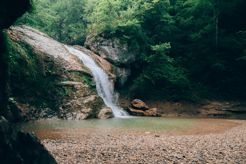 water falls on brown rocky river