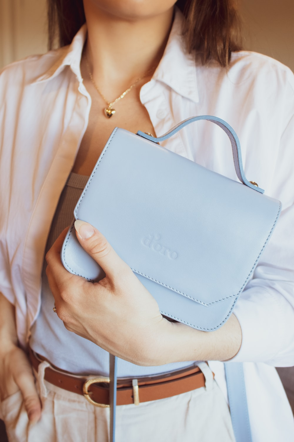 woman in white shirt holding white leather bag