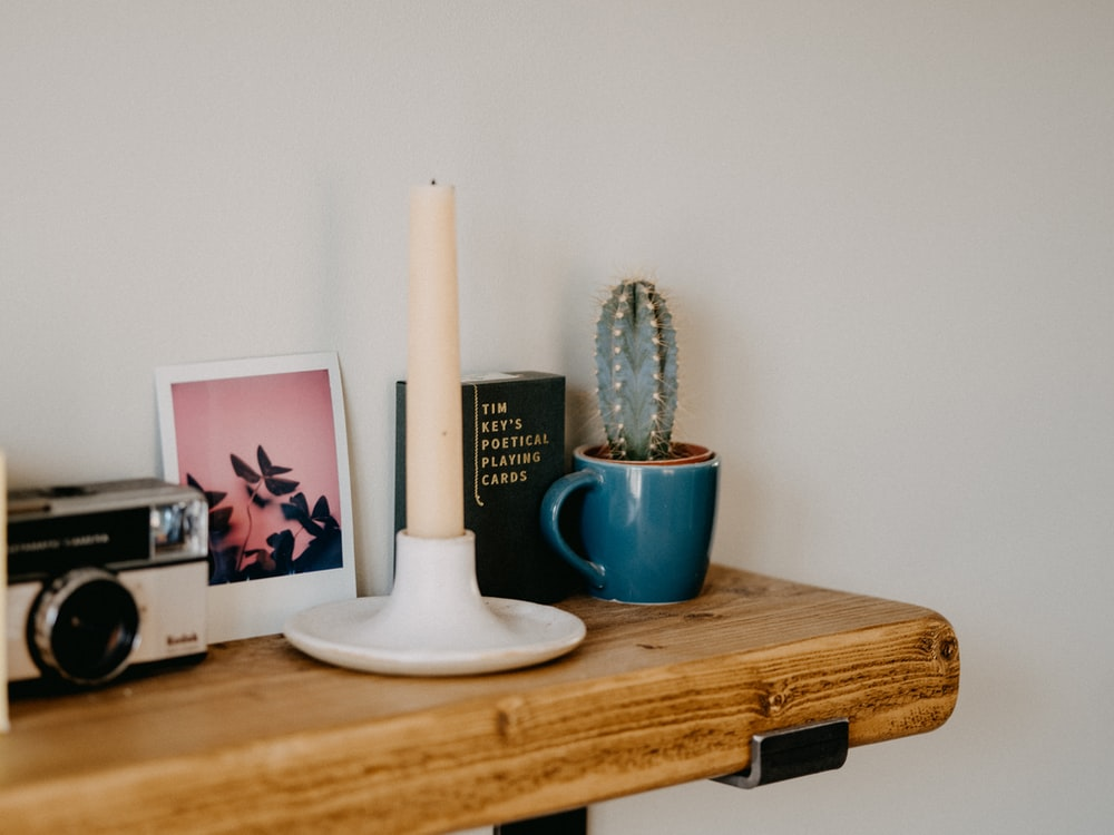 white ceramic candle holder on brown wooden table