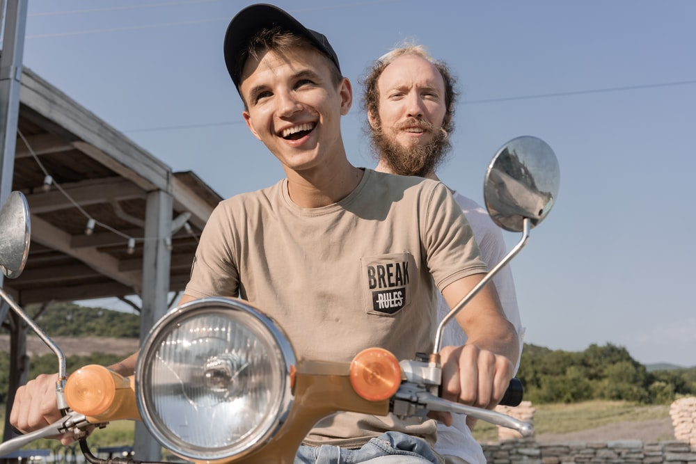 man in brown crew neck t-shirt holding silver balloons