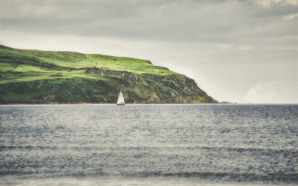 white sailboat on sea near green mountain under white clouds during daytime
