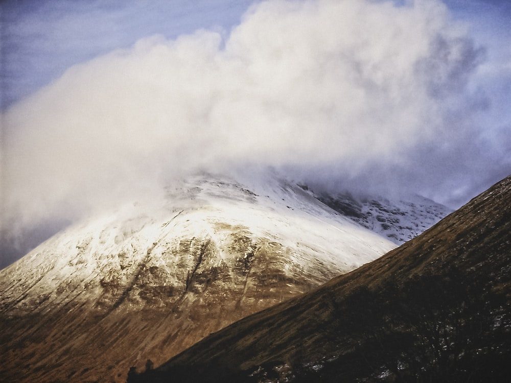 brown and white mountain under white clouds during daytime