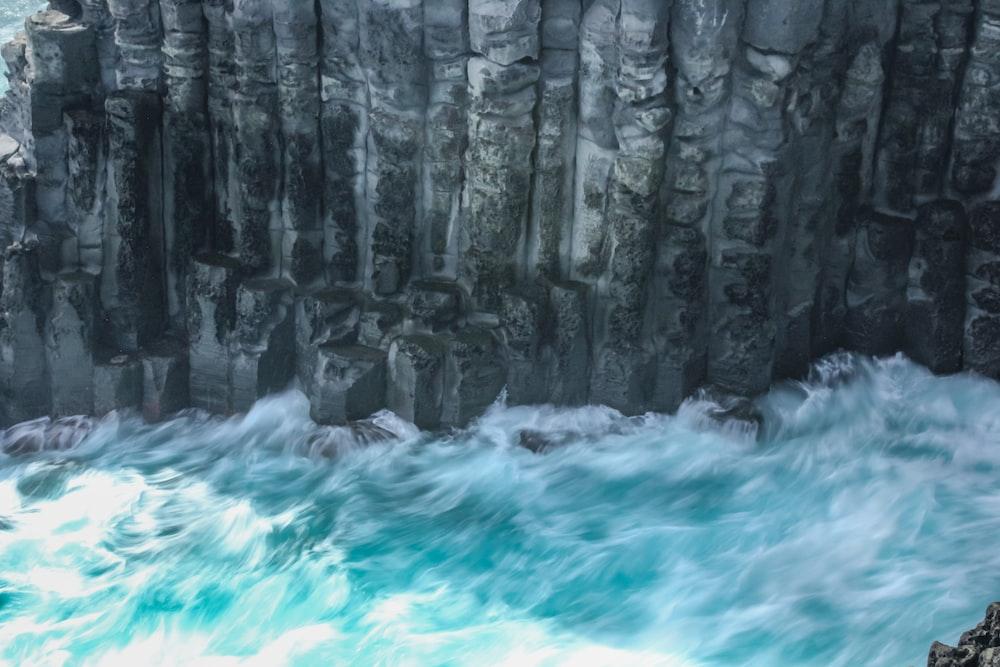 water waves hitting rocks during daytime