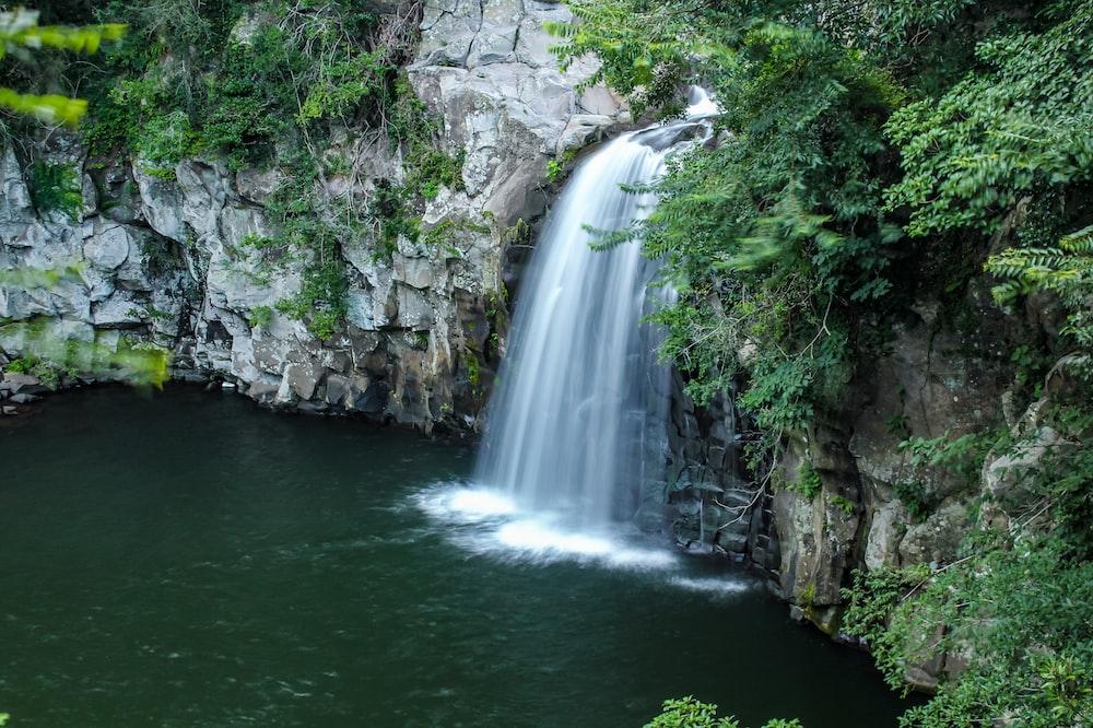 waterfalls between gray rocky mountain during daytime
