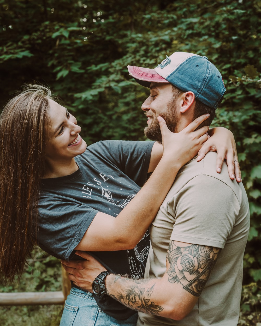 man in gray crew neck t-shirt kissing woman in blue denim cap