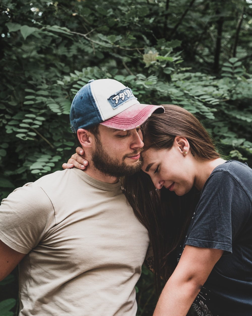 man in brown crew neck t-shirt kissing woman in blue cap