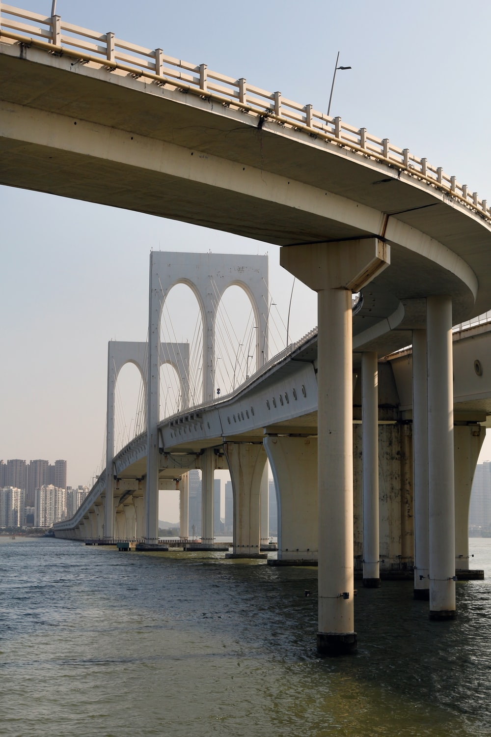white concrete bridge over body of water during daytime