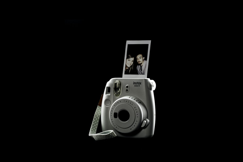 white and gray camera with picture of man in black suit