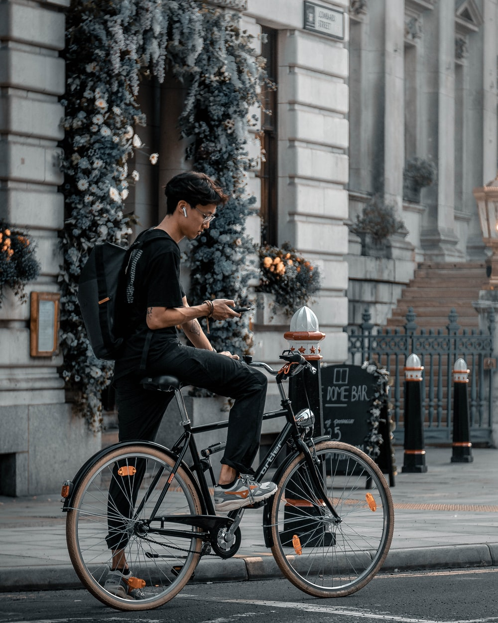 man in black t-shirt and black cap riding on black city bicycle