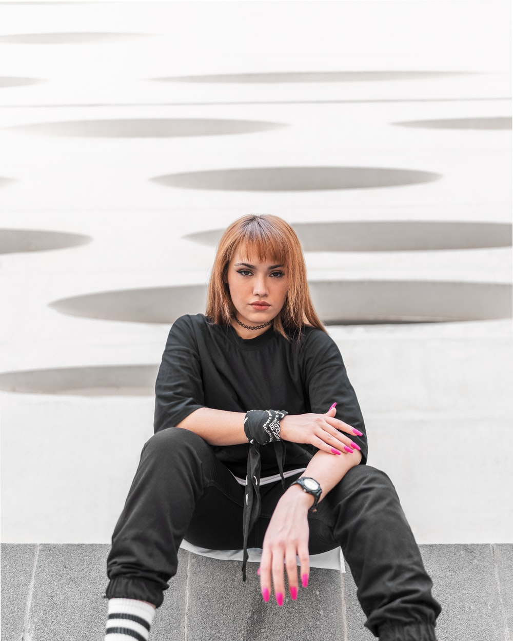 woman in black long sleeve shirt sitting on gray concrete stairs