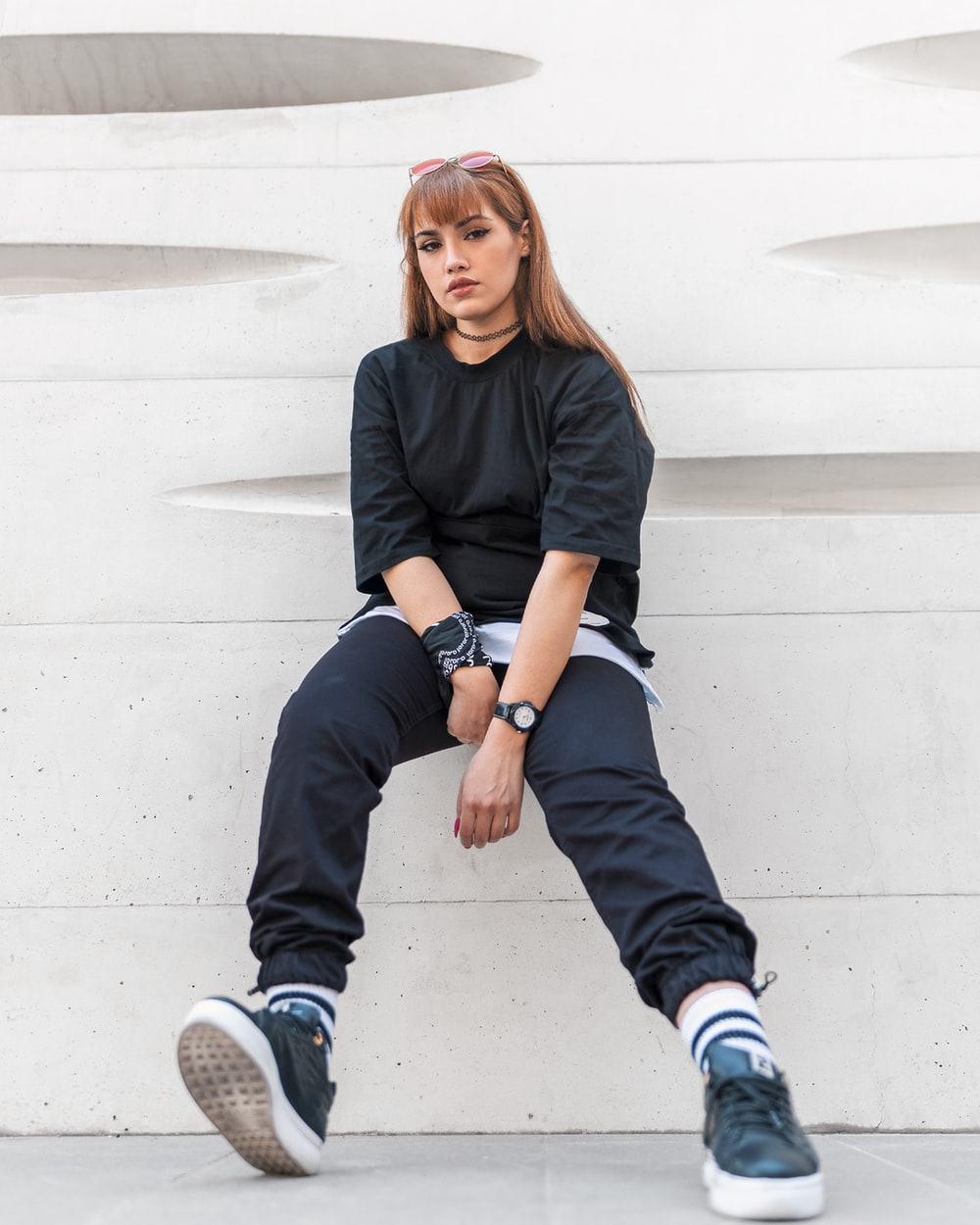 woman in black long sleeve shirt and blue denim jeans sitting on white concrete wall