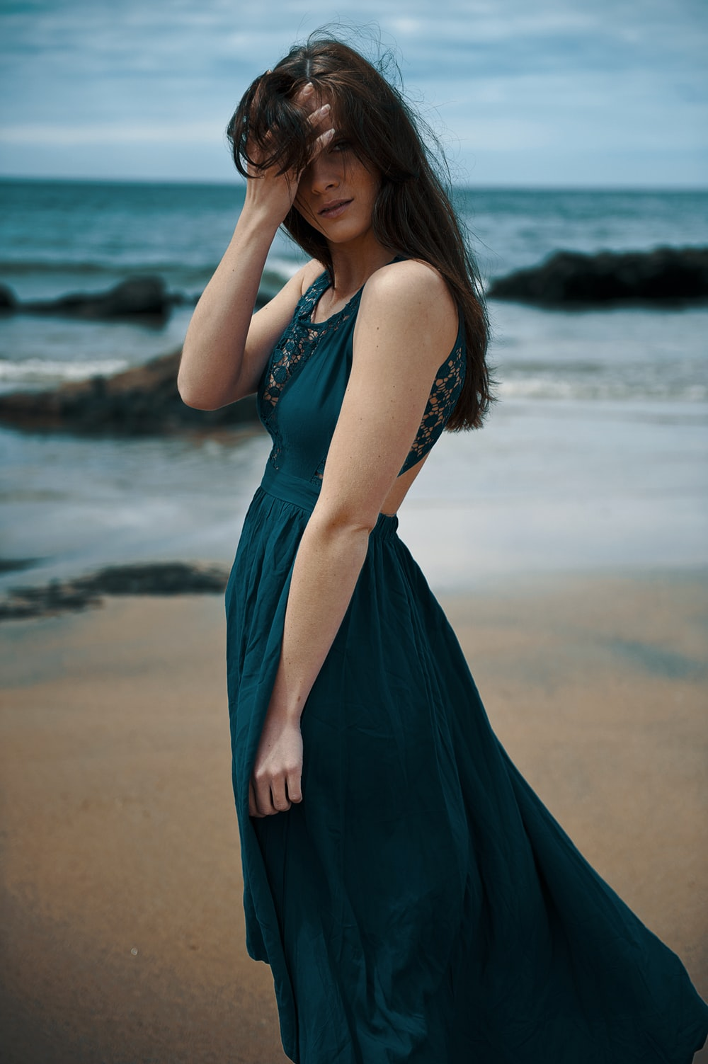 woman in blue sleeveless dress standing on beach during daytime