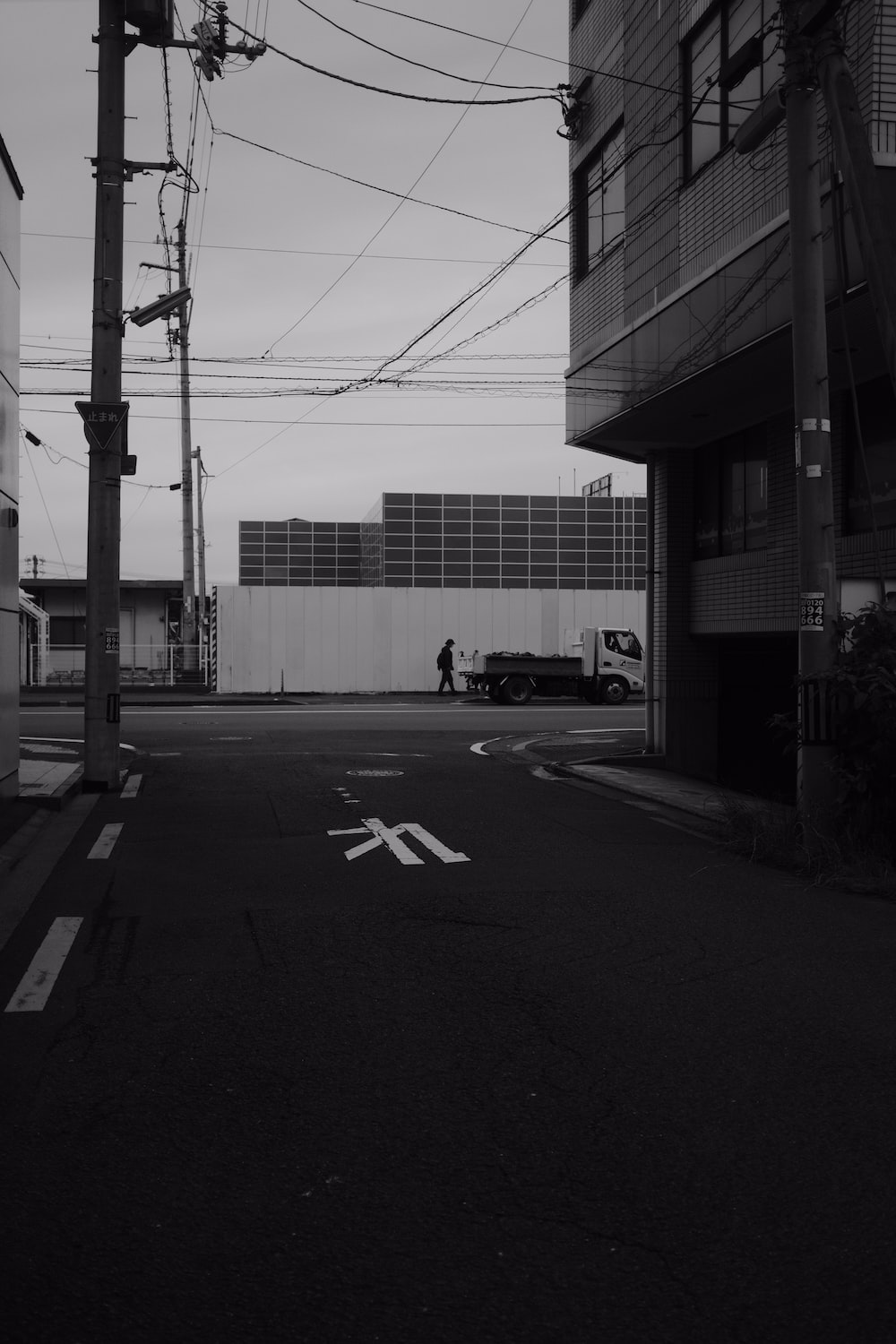 grayscale photo of a road with cars parked on the side