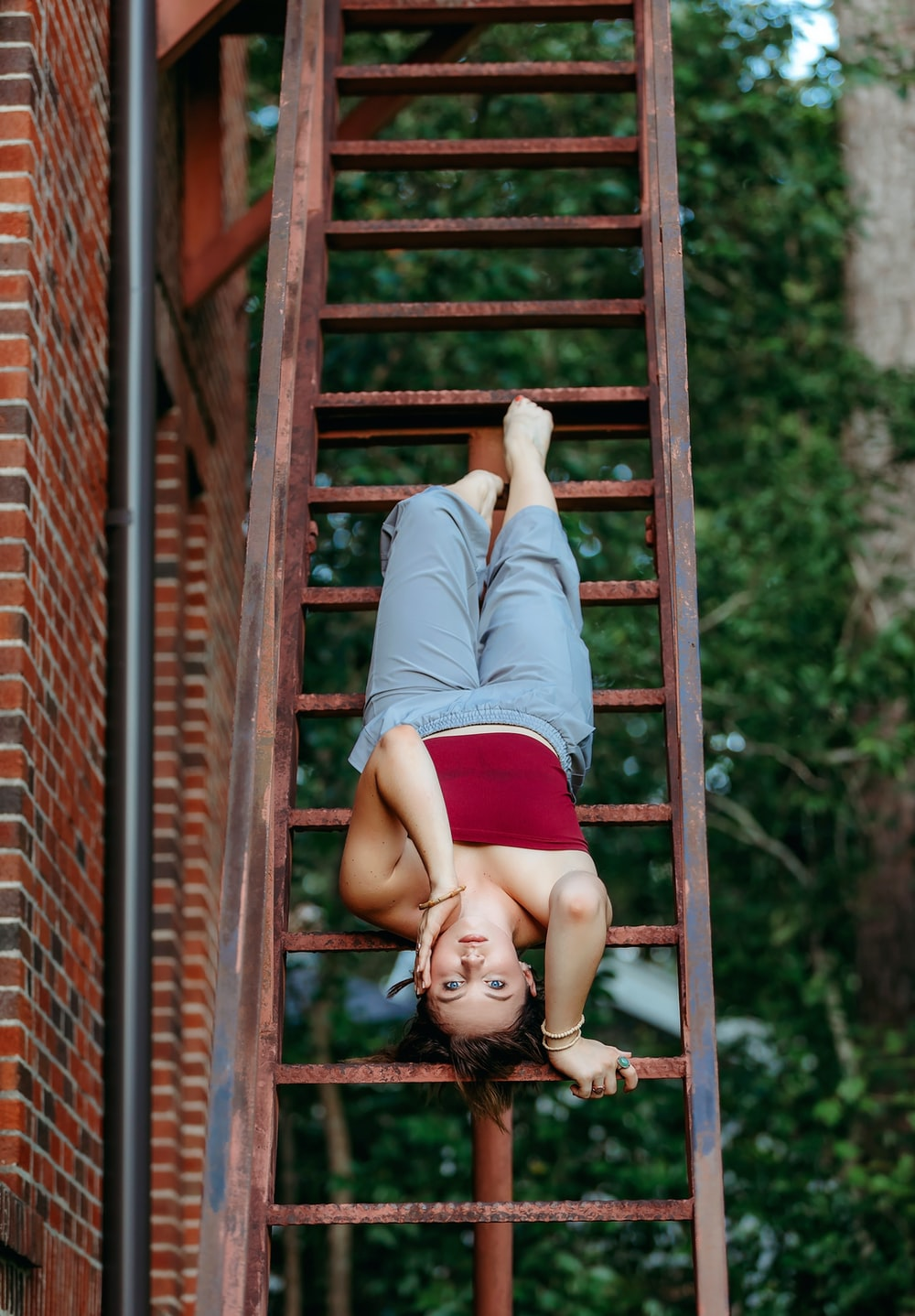 girl in blue and white long sleeve shirt and red skirt lying on brown wooden stairs