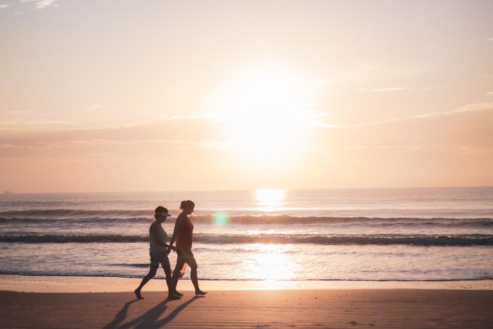 2 men standing on beach during sunset