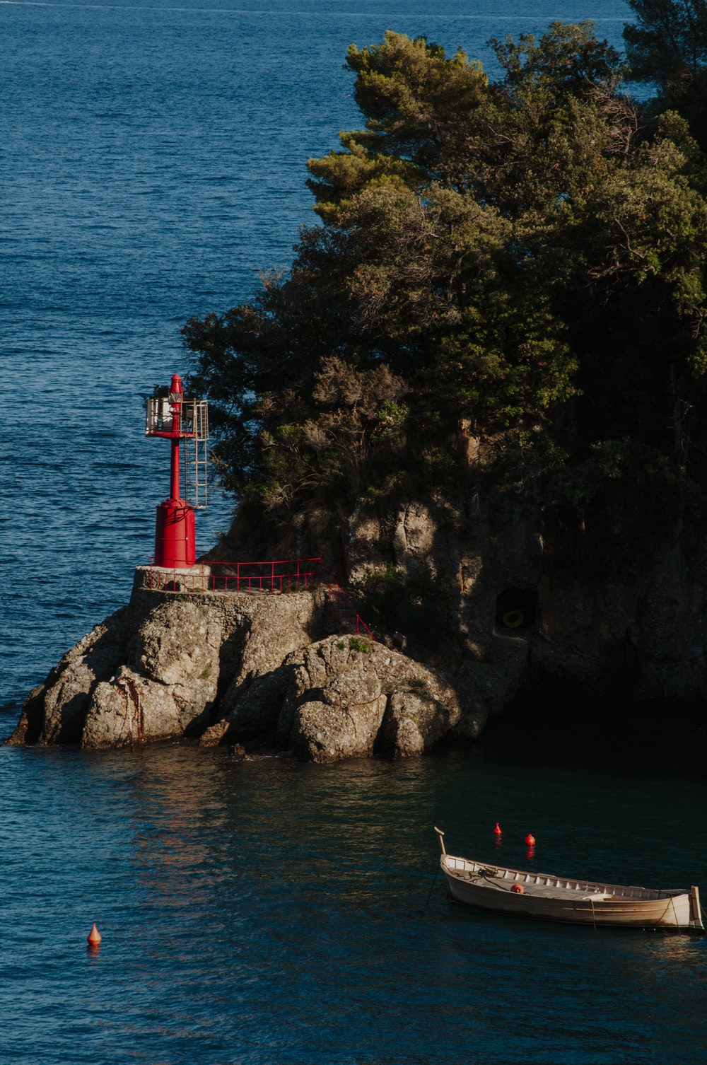 people on a rocky beach with a red tower in the distance