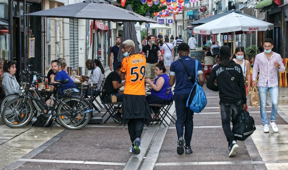 people in blue shirts riding on black metal cart during daytime
