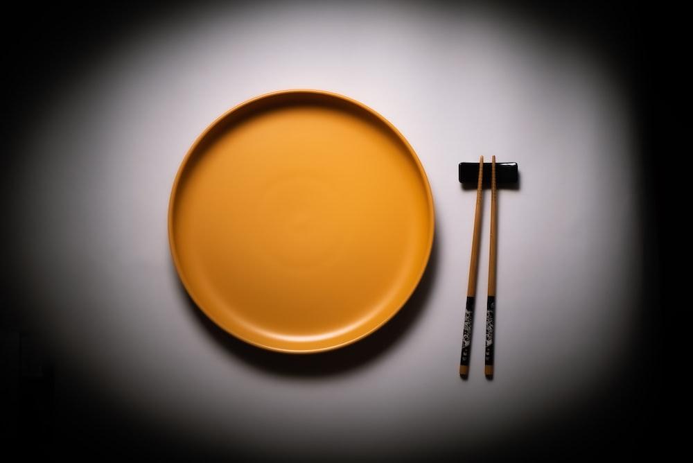 brown wooden sticks on round yellow ceramic plate